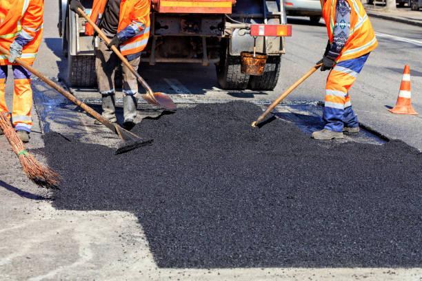 el equipo de trabajo suaviza el asfalto caliente con palas a mano al reparar la carretera. - obras civiles fotografías e imágenes de stock
