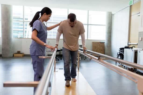 el paciente masculino toma los primeros pasos usando barras paralelas ortopédicas - salud ocupacional fotografías e imágenes de stock