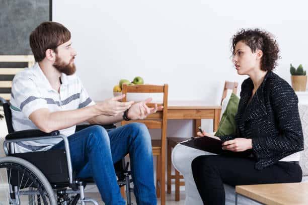 hombre en silla de ruedas con psicoterapeuta - salud ocupacional fotografías e imágenes de stock